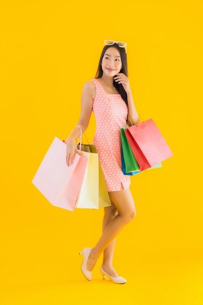 Retrato bela jovem mulher asiática com sacola colorida Foto gratuita