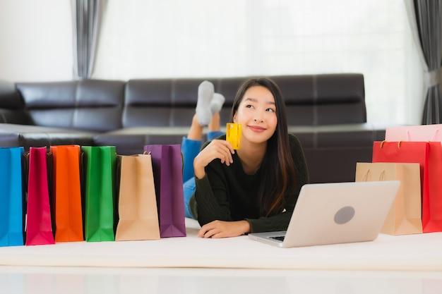 Retrato bela jovem mulher asiática com sacola de compras e cartão de crédito Foto gratuita