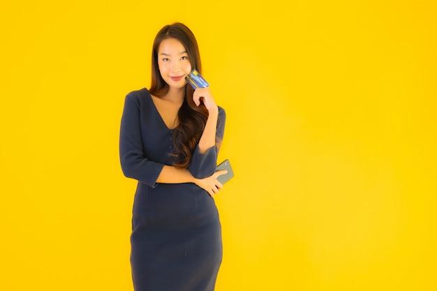 Retrato bela jovem mulher asiática com telefone e cartão de crédito Foto gratuita