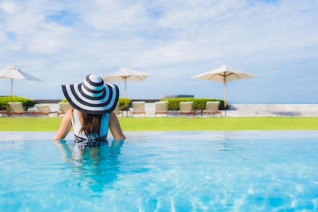 Retrato bela jovem mulher asiática em torno da piscina Foto gratuita