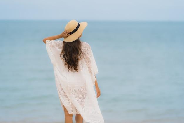 Retrato bela jovem mulher asiática sorriso feliz relaxar na praia mar oceano Foto gratuita