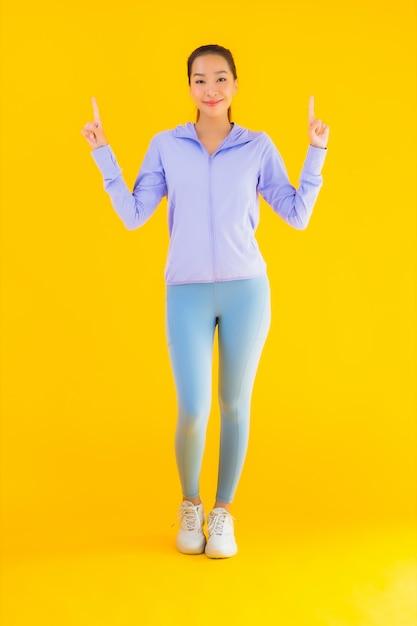 Retrato bela mulher asiática jovem esporte pronto para exercício amarelo Foto gratuita