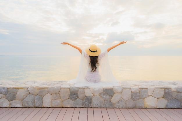 Retrato belas jovens mulheres asiáticas sorriso feliz relaxar ao redor do mar praia oceano Foto gratuita