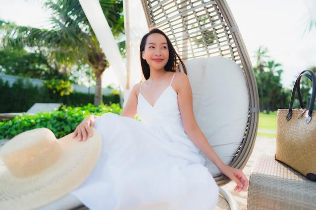 Retrato belas mulheres asiáticas em torno do oceano do mar praia com sorriso feliz Foto gratuita