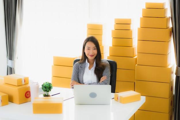 Retrato belo trabalho de mulher de negócios asiáticos em casa com o celular portátil com caixa de papelão pronta para o transporte Foto gratuita