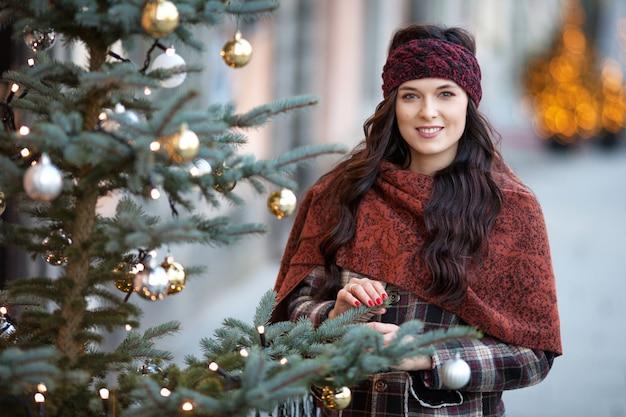 Retrato bonito alegre mulher em uma cidade. menina sorridente, vestindo roupas quentes e chapéu no inverno. Foto Premium