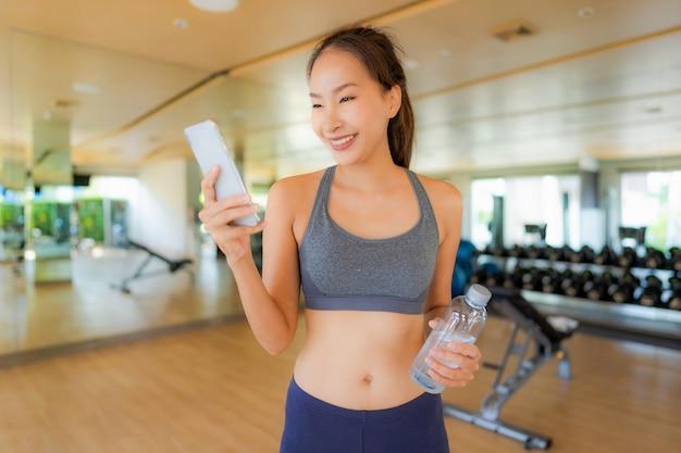 Retrato, bonito, asiático, mulher jovem, usando, telefone móvel, em, ginásio Foto gratuita