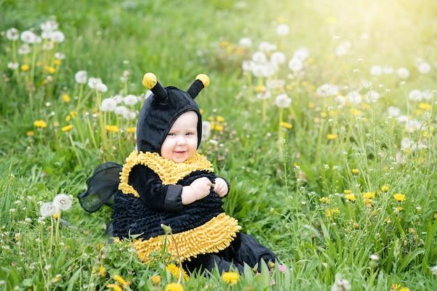 Retrato bonito e alegre da criança pequena que senta-se em flores de florescência do dente-de-leão no traje amarelo da abelha. Foto Premium