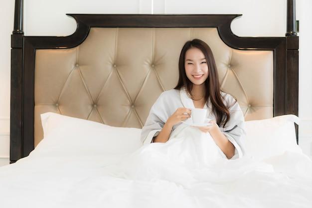 Retrato, bonito, jovem, mulher asian, acorde, com, feliz, sorrizo, e, xícara café, cama, em, quarto, inter Foto gratuita