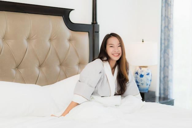 Retrato, bonito, jovem, mulher asian, acorde feliz, e, sorrizo, cama, em, quarto, interior Foto gratuita