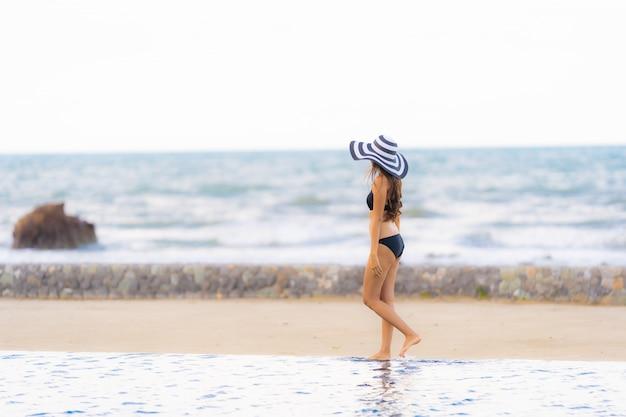 Retrato, bonito, jovem, mulher asian, desgaste, biquíni, ao redor, piscina, em, hotel, recurso, quase, mar oceano, praia Foto gratuita