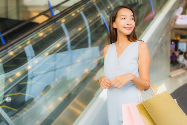 Retrato, bonito, jovem, mulher asian feliz, e, sorrizo, com, saco shopping, de, loja de departamentos Foto gratuita