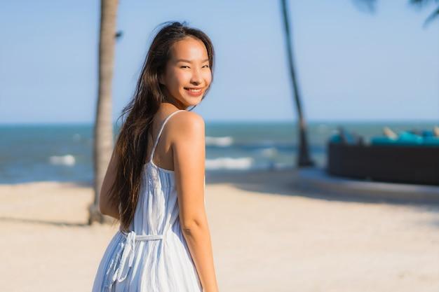 Retrato, bonito, jovem, mulher asian, feliz, sorrizo, relaxe, ao redor, neary, praia, e, mar Foto gratuita