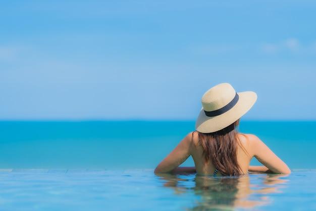 Retrato, bonito, jovem, mulher asian, feliz, sorrizo, relaxe, em, piscina, em, hotel, recurso, neary, mar, oceânicos, praia, ligado, céu azul Foto gratuita