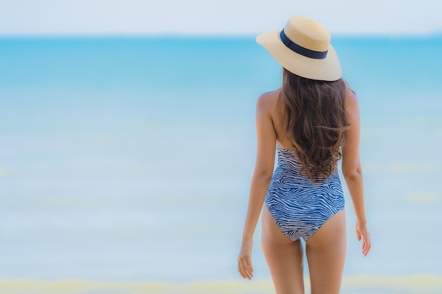 Retrato, bonito, jovem, mulher asian, feliz, sorrizo, relaxe, ligado, a, praia tropical, mar, oceânicos, para, lazer, viagem Foto gratuita