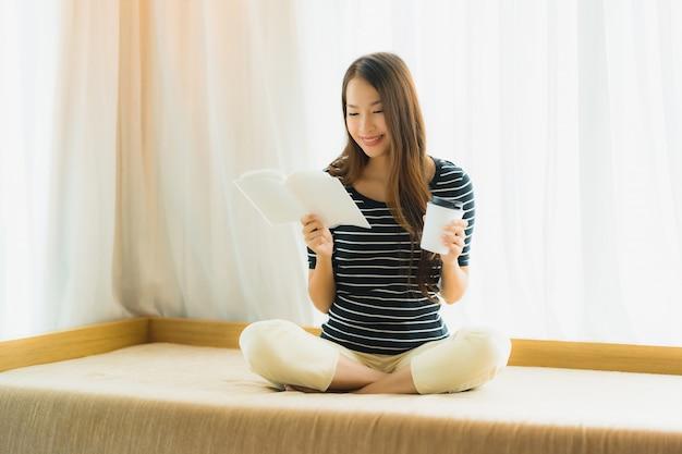 Retrato, bonito, jovem, mulher asian, livro leitura, e, xícara café segurar, ou, assalte, ligado, ligado, sofá, em, sala de estar, área Foto gratuita