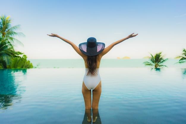 Retrato, bonito, jovem, mulher asian, relaxe, em, luxo, piscina ao ar livre, em, hotel, recurso, quase, praia, mar, oceânicos Foto gratuita