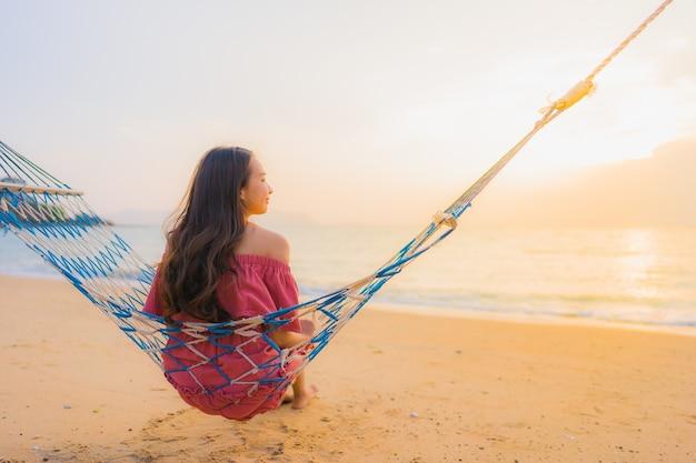 Retrato, bonito, jovem, mulher asian, sentando, ligado, a, rede, com, sorrizo, feliz, neary, mar praia, e, oce Foto gratuita