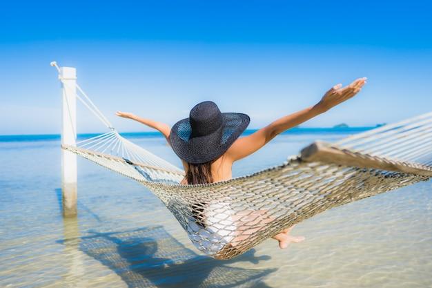 Retrato, bonito, jovem, mulher asian, sentando, ligado, rede, ao redor, mar, praia, oceânicos, para, relaxe Foto gratuita
