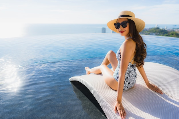 Retrato, bonito, jovem, mulher asian, sorrizo, feliz, relaxe, ao redor, piscina, em, hotel, recurso, para, lazer Foto gratuita
