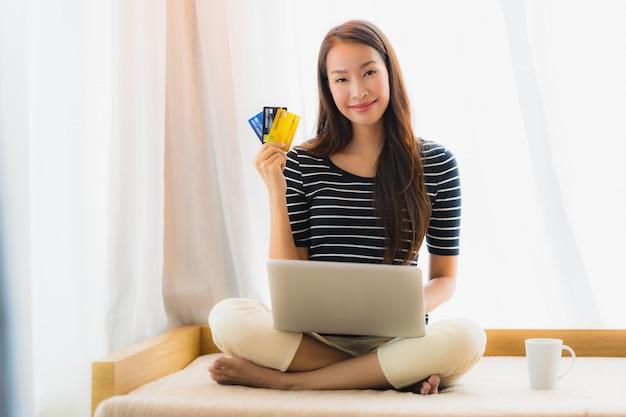Retrato, bonito, jovem, mulher asian, usando computador, caderno, ou, laptop, com, cartão crédito, para, shopping Foto gratuita
