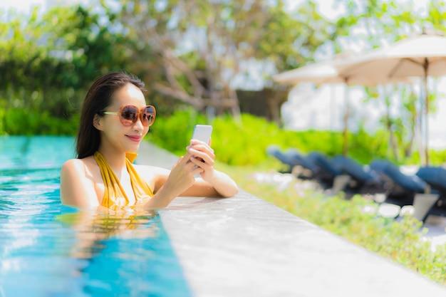 Retrato, bonito, jovem, mulher asian, usando, telefone móvel, ou, cellphone, em, a, piscina Foto gratuita