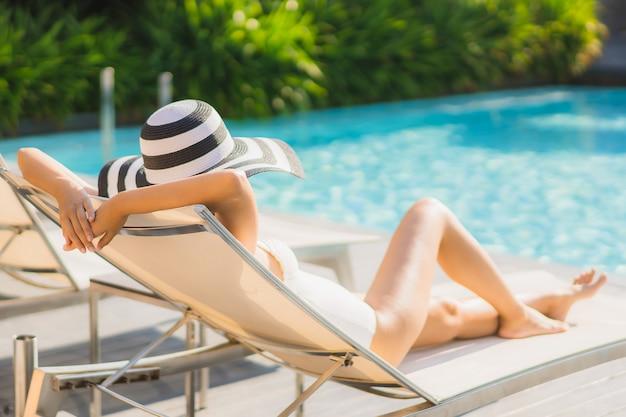 Retrato bonito jovem mulher asiática feliz sorrir e relaxar em torno da piscina no hotel resort Foto gratuita