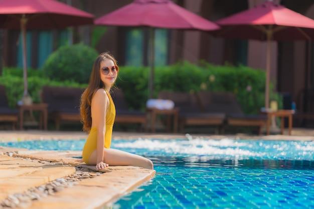 Retrato bonito jovem mulher asiática lazer relaxar sorriso e feliz ao redor da piscina no hotel resort Foto gratuita