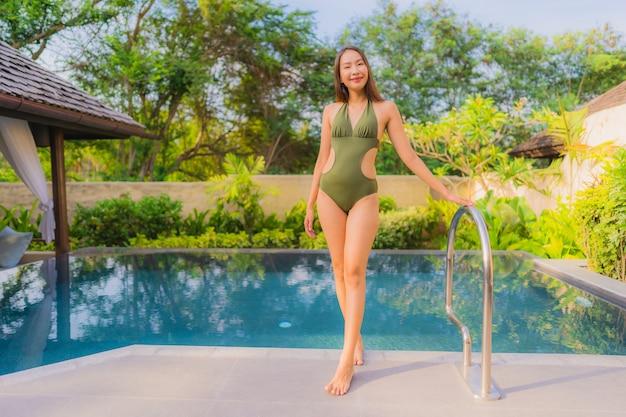 Retrato bonito jovem mulher asiática sorriso feliz relaxar e lazer na piscina Foto gratuita