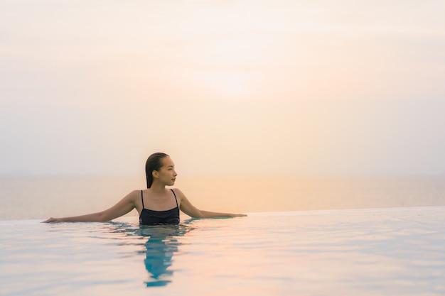 Retrato bonito jovem mulher asiática sorriso feliz relaxar em torno da piscina no hotel resort Foto gratuita