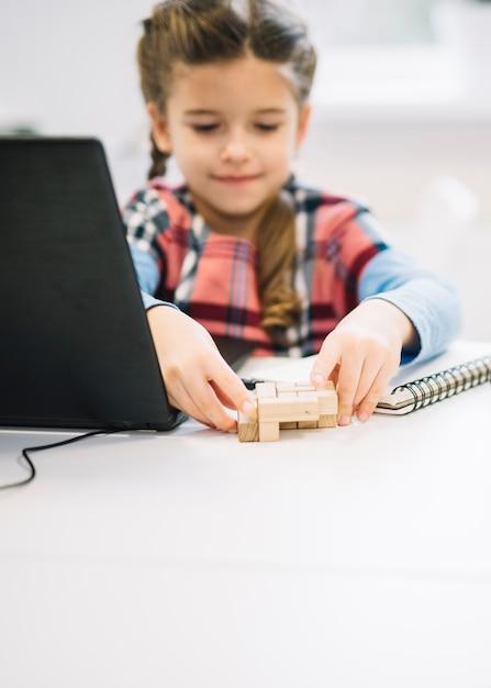 Retrato borrado de uma menina brincando com quebra-cabeça de madeira na mesa branca Foto gratuita