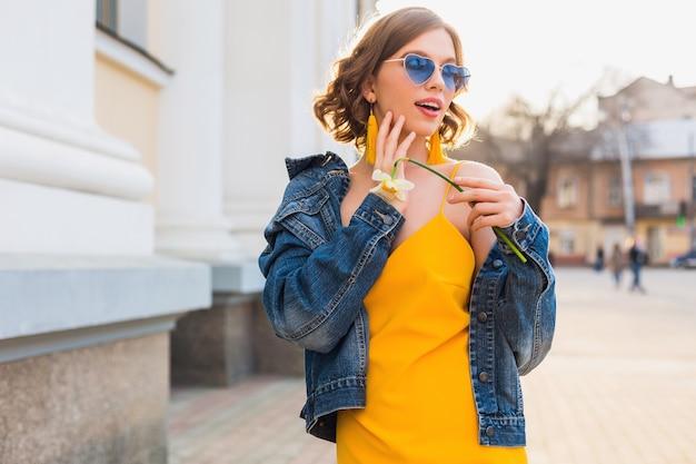 Retrato brilhante de uma linda mulher segurando uma flor, vestido amarelo, jaqueta jeans, estilo moderno, tendência da moda de verão, sorriso, óculos de sol da moda Foto gratuita