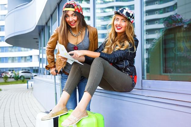 Retrato brilhante do estilo de vida ao ar livre das duas melhores amigas caminhando com suas malas perto do aeroporto Foto gratuita