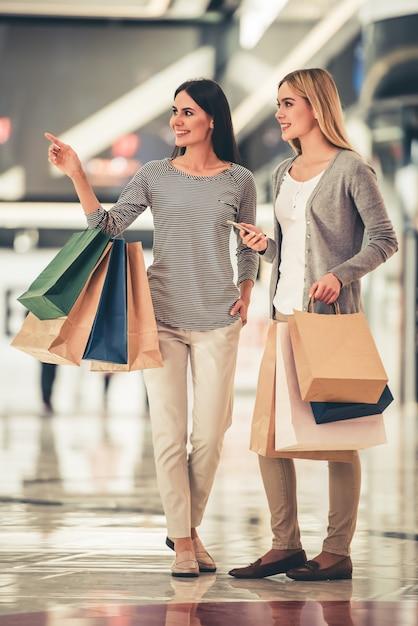 Retrato cheio do comprimento de meninas bonitas com sacos de compras. Foto Premium