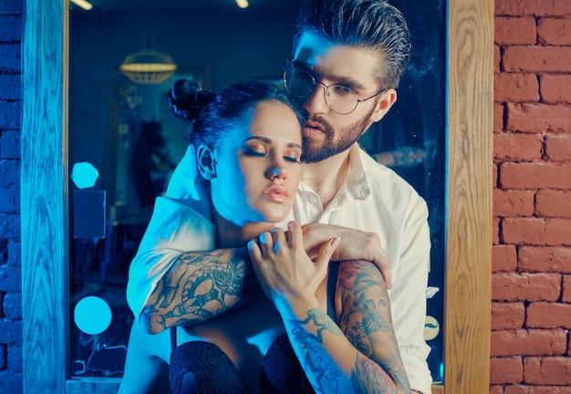 Retrato colorido de lindo casal: homem brutal em um terno elegante e garota com uma tatuagem de lingerie na barbearia Foto gratuita