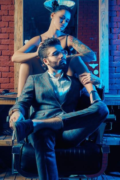 Retrato colorido de lindo casal: homem brutal em um terno elegante e uma garota sexy com uma tatuagem de lingerie na barbearia Foto Premium