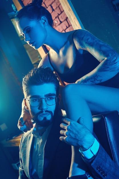 Retrato colorido de lindo casal. homem de terno elegante e garota com uma tatuagem de lingerie na barbearia Foto Premium