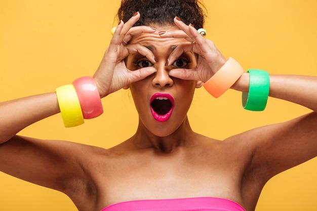 Retrato colorido de mulher adorável de raça mista com maquiagem moda e jóias nas mãos, olhando para a câmera pelos dedos isolados, sobre parede amarela Foto gratuita