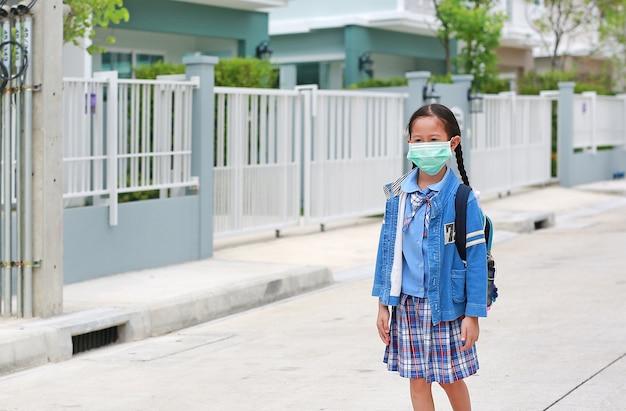 Retrato criança asiática menina em uniforme escolar, vestindo máscara médica caminhando ao ar livre sair de casa para ir para a escola. Foto Premium