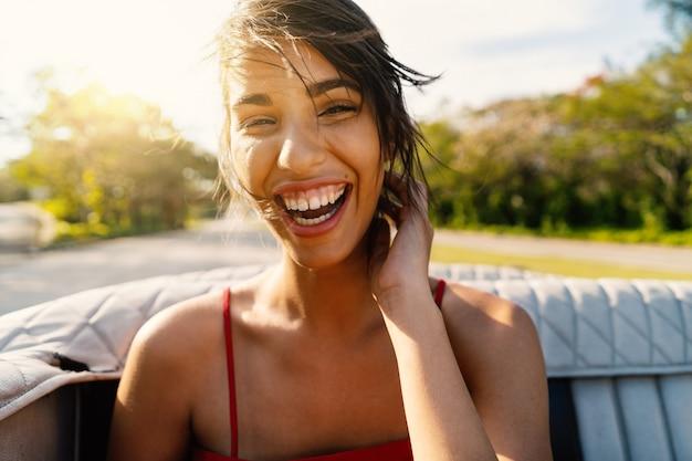 Retrato cubano de riso bonito da mulher em um carro do cabriolet do vintage em cuba. imagem do estilo de vida real em um dia ensolarado com reflexões do alargamento. Foto Premium