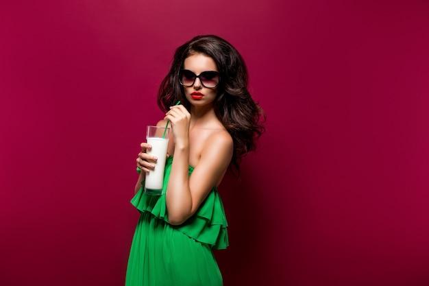 Retrato da bela jovem morena de óculos escuros e vestido verde com coquetel Foto Premium