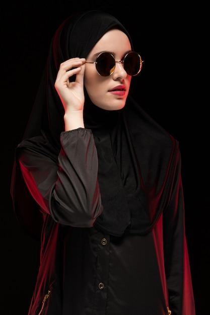 Retrato da bela jovem muçulmana elegante vestindo preto hijab e óculos de sol como conceito moderno de moda oriental, posando em fundo preto Foto Premium