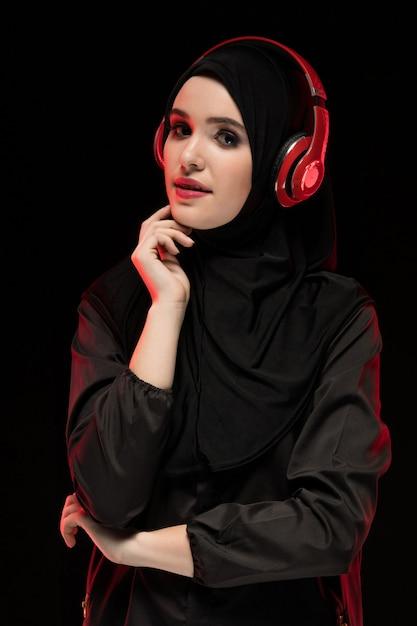 Retrato da bela jovem muçulmana inteligente vestindo preto hijab ouvindo música em fones de ouvido Foto Premium