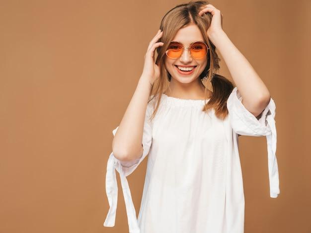 Retrato da bela modelo bonitinho sorridente com lábios rosa. garota de vestido branco do verão. modelo posando em óculos de sol Foto gratuita