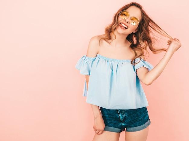 Retrato da bela modelo bonito sorridente em óculos de sol redondos. garota com roupas coloridas do verão. levantamento modelo Foto gratuita