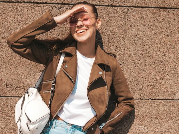 Retrato da bela modelo moreno sorridente, vestido com roupas de jeans e jaqueta hipster de verão Foto gratuita