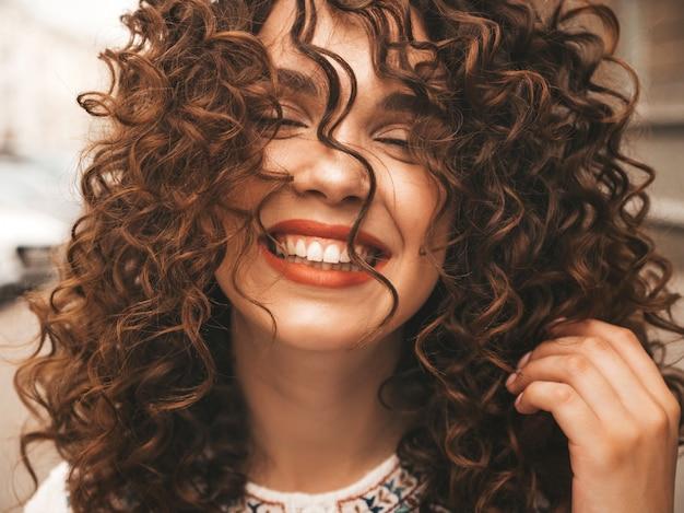 Retrato da bela modelo sorridente com penteado afro cachos. Foto gratuita