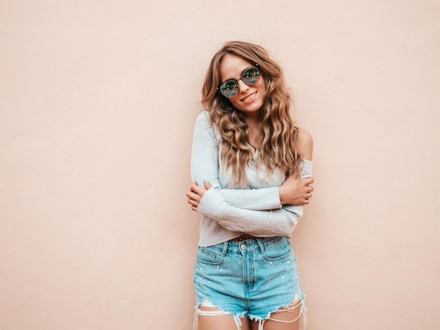 Retrato da bela modelo sorridente, vestido com roupas de shorts jeans hipster de verão. Foto gratuita