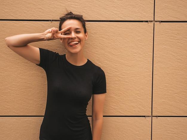 Retrato da bela modelo sorridente, vestido com roupas de verão. menina na moda posando na rua. mulher engraçada e positiva se divertindo, mostra língua e sinal de paz Foto gratuita