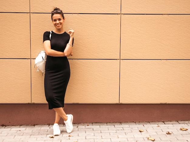 Retrato da bela modelo sorridente, vestido com roupas de verão. menina na moda posando na rua. mulher engraçada e positiva se divertindo Foto gratuita